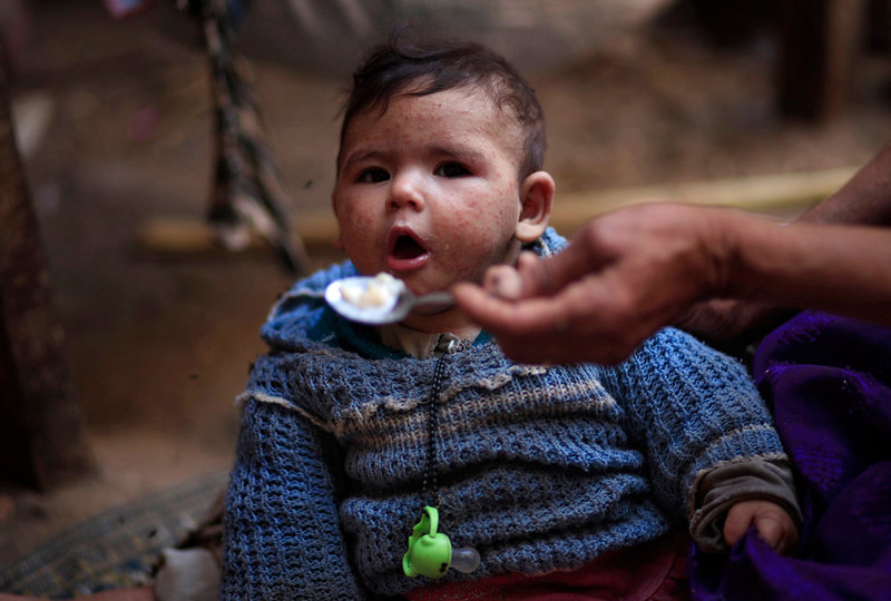 . An elderly Palestinian refugee woman feeds a baby suffering from heat rash in a house in Gezirat al-Fadel village, Sharqiya, about 150 kilometers (93 miles) east of Cairo, Egypt.  (AP Photo/Khalil Hamra)