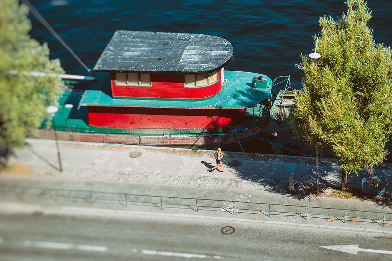 On a sunny morning a woman jogs by a red and green boat.