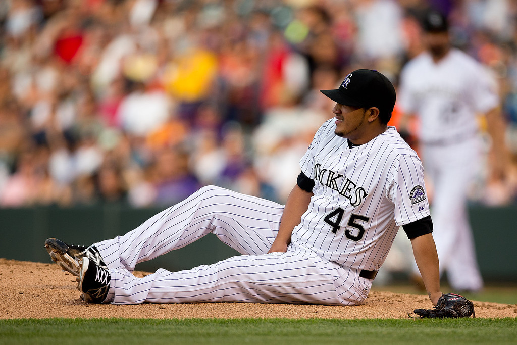 . Starting pitcher Jhoulys Chacin #45 of the Colorado Rockies lies on the ground after being hit with the ball on a base hit off the bat of Adeiny Hechavarria #3 of the Miami Marlins during the third inning at Coors Field on July 23, 2013 in Denver, Colorado.  (Photo by Justin Edmonds/Getty Images)