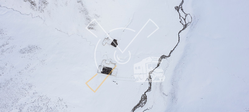 Aerial abstract image showing farms in the central-asian Tian Shan mountains covered in snow,