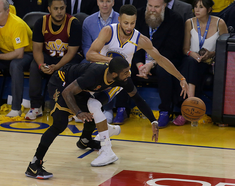 . Cleveland Cavaliers guard Kyrie Irving, bottom, reaches for the ball under Golden State Warriors guard Stephen Curry during the first half of Game 5 of basketball\'s NBA Finals in Oakland, Calif., Monday, June 12, 2017. (AP Photo/Ben Margot)