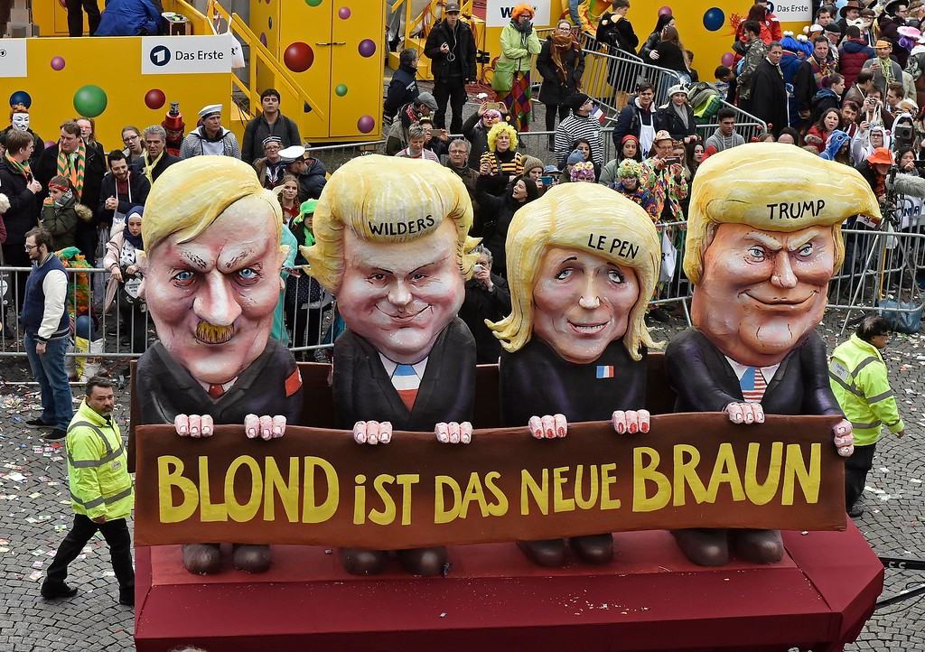 . A carnival float depicting, from left, Adolf Hitler, Geert Wilders, Marine Le Pen and U.S. President Donald Trump reading \'blonde is the new brown\' is driven through the streets at the traditional carnival parade in Duesseldorf, Germany, Monday, Feb. 27, 2017. The foolish street spectacles in the carnival centers of Duesseldorf, Mainz and Cologne, watched by hundreds of thousands of people, are the highlights in Germany\'s carnival season on Rose Monday. (AP Photo/Martin Meissner)