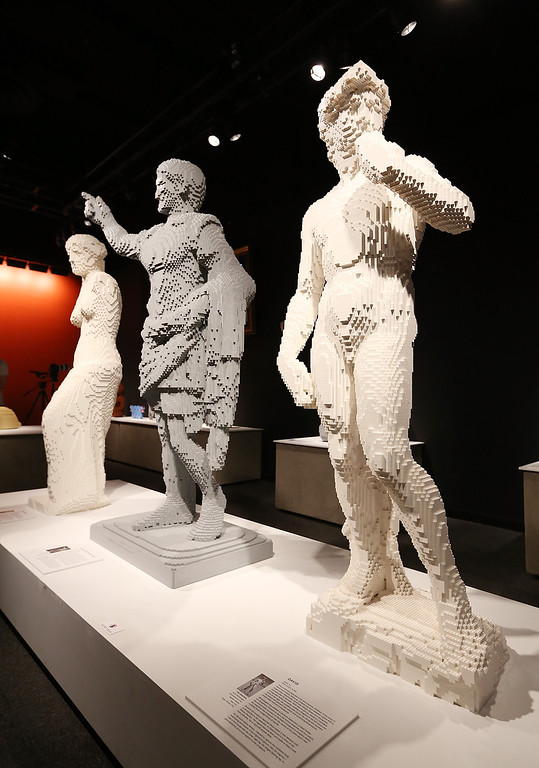. (R) a Nathan Sawaya sculpture, is displayed with others in the \'Art of the Brick\' show at Discovery Times Square on June 18, 2013 in New York City.  (Photo by Mario Tama/Getty Images)