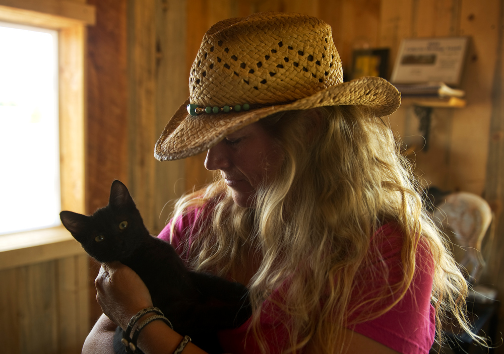 . Lenny and Sara Martinelli  at their Three Leaf Concepts Farm in Lafayette on Wednesday, July 3, 2013.  They have horses, chickens, goats and are raising vegetables for their restaurants. Sara holds a kitten up in her office at the farm. (Photo By Cyrus McCrimmon/The Denver Post)