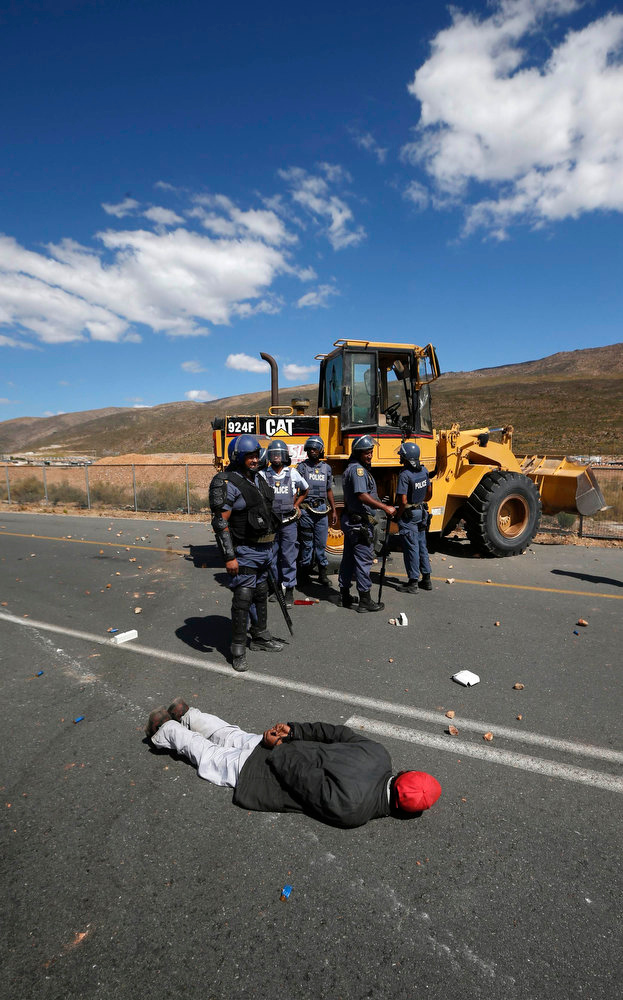. Police stand around an arrested demonstrator during a farm workers strike at De Doorns on the N1 highway linking Cape Town and Johannesburg, January 10, 2013 . Police fired rubber bullets and stun grenades at hundreds of striking farm workers who blocked a highway in the grape-growing Western Cape on Thursday, the first clashes of a year likely to be marked by fractious labour relations.  Hundreds of striking workers seeking higher wages and better working conditions again blocked a major highway running through the town of De Doorns, about 100 kms (60 miles) east of Cape Town, hurling stones at motorists. REUTERS/Mike Hutchings