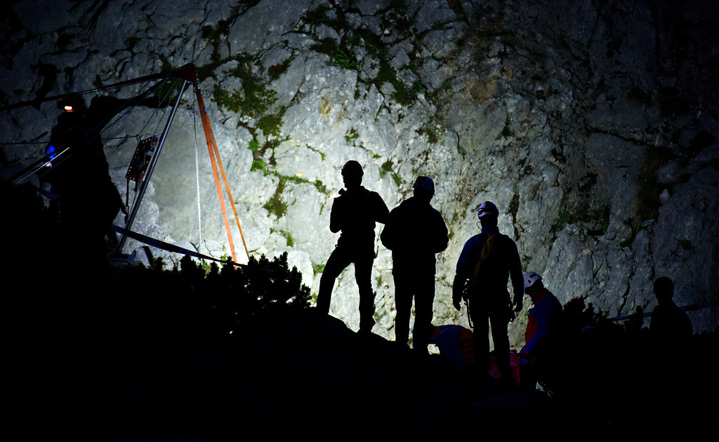 . Members of the mountain rescue service stand next to the entrance of the Riesending cave near Marktschellenberg, southern Germany,  early Thursday June  19, 2014.  (AP Photo/dpa,Nicolas Armer)