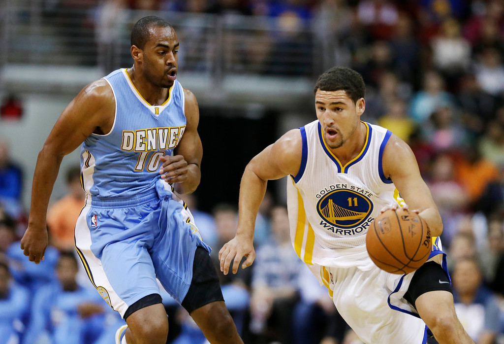 . Golden State Warriors guard Klay Thompson, right, drives past Denver Nuggets guard Arron Afflalo during the first half of a preseason NBA basketball game, Thursday, Oct. 16, 2014, in Des Moines, Iowa. (AP Photo/Charlie Neibergall)