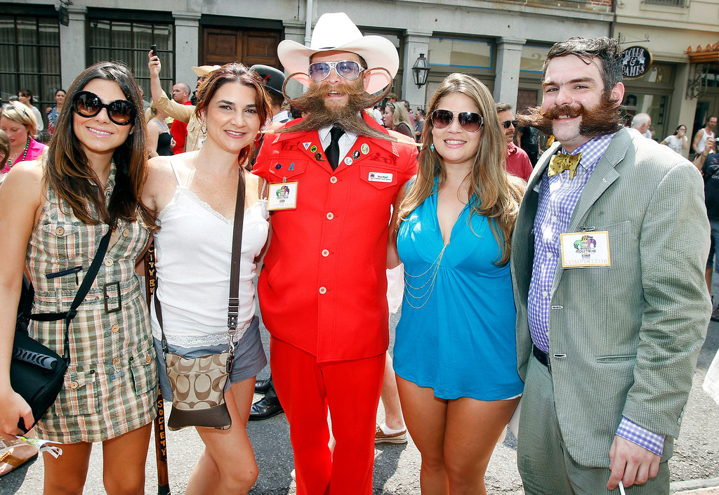 . Tourists Elaine Oliveira, Zuleika Riveron and Daniele Alfonso pose with contestants Paul Roof of Charleston, South Carolina and Derek Nehrbass of New Orleans during a parade through the French Quarter kicking off the fourth annual Just For Men National Beard and Moustache Championships Saturday, Sept. 7, 2013 in New Orleans. Contestants competed in 18 different categories including Dali, full beard natural and sideburns. (AP Photo/Susan Poag)