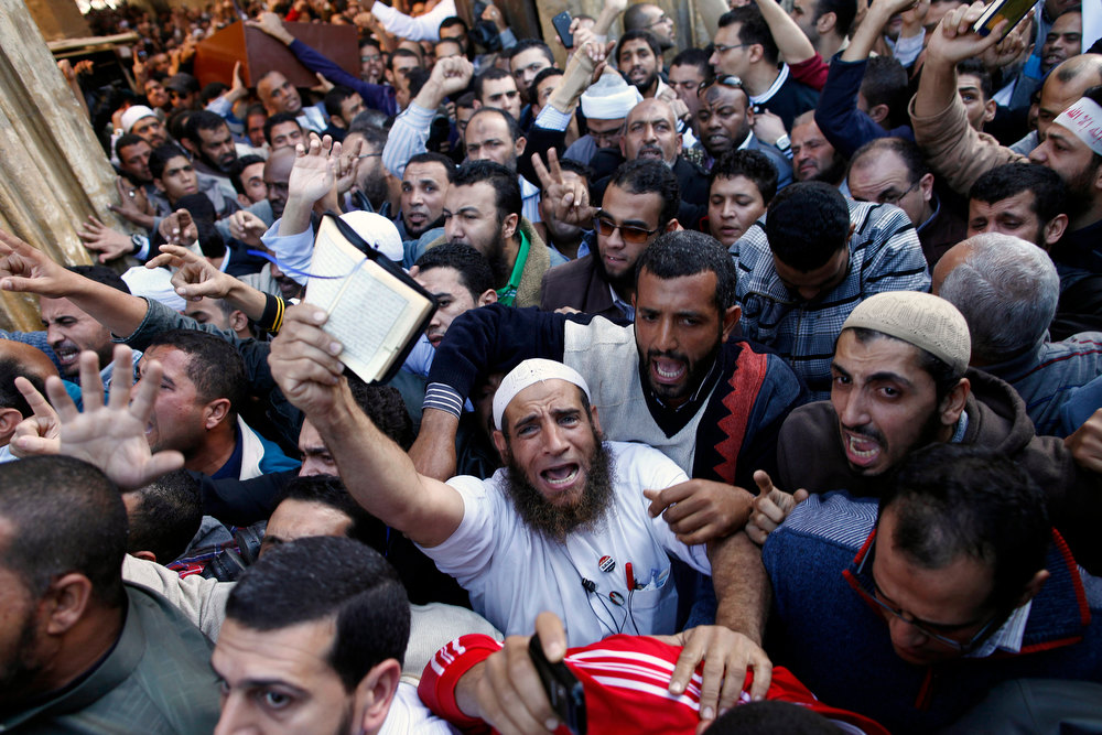 . Egyptians shout slogans during the funeral of a supporter of President Mohamed Morsi in Cairo, on December 7, 2012. Seven people died in clashes between Morsi\'s Islamist supporters and his mainly secular opponents on in Egypt\'s worst political crisis since Morsi took office in June. MAHMOUD KHALED/AFP/Getty Images