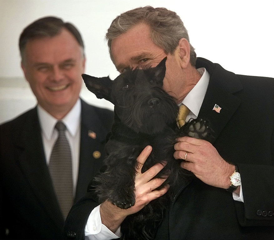". President Bush holds up his dog, Barney, and waves his paw to members of the media during his arrival at the South Lawn of the White House in this Wednesday, Feb. 27, 2002 file photo in Washington. In the back Gary Walters, chief usher at the White House. The chief usher of the Executive Mansion, Walters is retiring after more than 30 years _ and taking with him an intimate knowledge of everyday life at 1600 Pennsylvania Ave. ""We have known Gary for many years and are especially grateful for making our family feel at home,\"" President Bush and first lady Laura Bush said in a statement Tuesday, Oct. 24, 2006.  (AP Photo/Pablo Martinez Monsivais, File)"