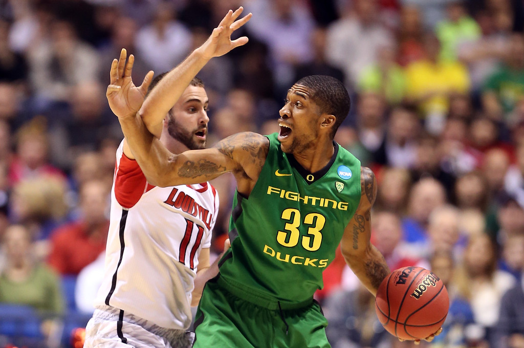 . Carlos Emory #33 of the Oregon Ducks looks to pass the ball in the first half as he is defended by Luke Hancock #11 of the Louisville Cardinals during the Midwest Region Semifinal round of the 2013 NCAA Men\'s Basketball Tournament at Lucas Oil Stadium on March 29, 2013 in Indianapolis, Indiana.  (Photo by Andy Lyons/Getty Images)