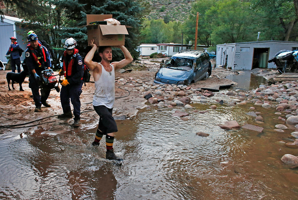 . Local resident Chris Rodes gets help from emergency responders as he helps salvage a friend\'s belongings after floods left homes and infrastructure in a shambles Lyons, Colo., Friday Sept. 13, 2013.  (AP Photo/Brennan Linsley)
