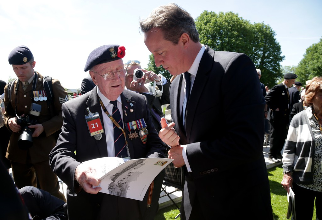 . Prime Minister David Cameron stops to chat with veterans at Bayeux Cemetery during D-Day 70th anniversary commemorations on June 6, 2014 in Bayeux, France.  (Photo by Matt Cardy/Getty Images)