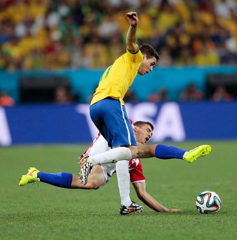 . Brazil\'s Oscar collides with Croatia\'s Mateo Kovacic during the group A World Cup soccer match between Brazil and Croatia, the opening game of the tournament, in the Itaquerao Stadium in Sao Paulo, Brazil, Thursday, June 12, 2014.  (AP Photo/Ivan Sekretarev)
