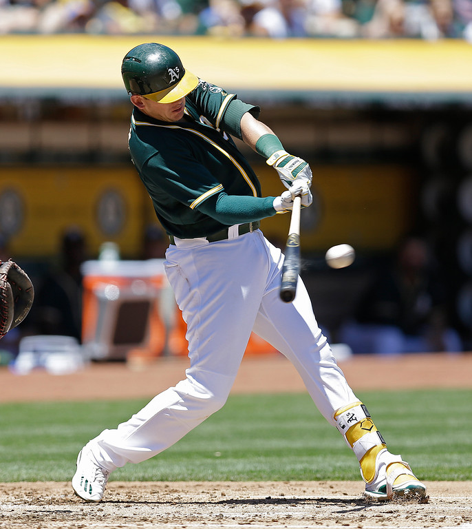 . Oakland Athletics\' Ryon Healy connects for a two run single off Cleveland Indians\' Trevor Bauer in the first inning of a baseball game, Sunday, July 16, 2017, in Oakland, Calif. (AP Photo/Ben Margot)