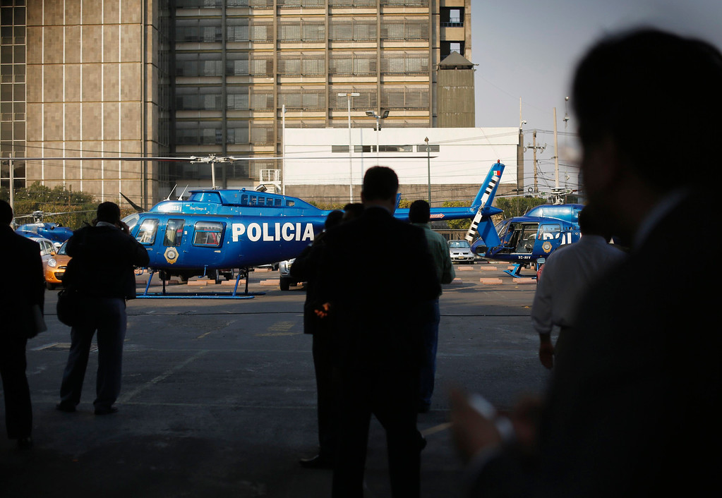 . Police helicopters are stationed in the parking lot of state oil giant Pemex in Mexico City January 31, 2013. A powerful explosion rocked the Pemex building on Thursday, killing at least 14 people and injuring 100 others. The blast hit the lower floors of the downtown tower block, throwing debris into the streets and sending workers running outside.  REUTERS/Tomas Bravo