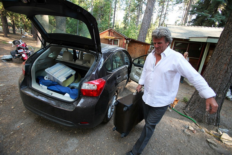 . Pat Moloney packs up to evacuate from his home on Saunders Meadow Rd in Idyllwild, Calif., as the Mountain Fire approaches the mountain town, Wednesday, July 17, 2013. (AP Photo/The Desert Sun, Richard Lui)