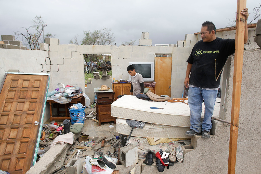 . Raimundo Diaz Cruz, right, and his son, also named Raimundo Diaz, 17, salvage wood beans and bricks to rebuild their house after it was destroyed by Hurricane Odile in Los Cabos, Mexico,  Monday, Sept. 15, 2014. (AP Photo/Victor R. Caivano)