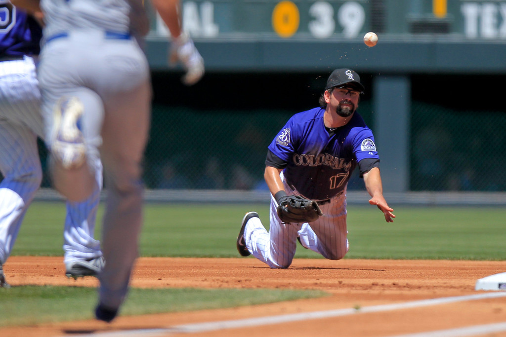 . Colorado Rockies\' Todd Helton (17) tosses the ball to Jhoulys Chacin after making a diving stop on a line drive by Los Angeles Dodgers\' Mark Ellis (14) during the first inning of the MLB National League baseball game Saturday, June 1, 2013 in Denver. (AP Photo/Barry Gutierrez)