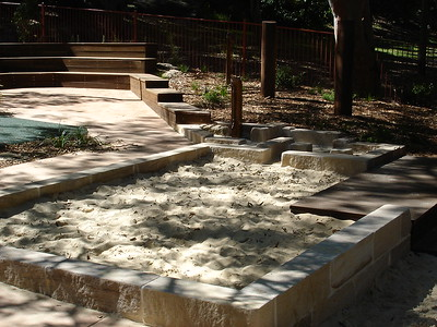 sandpit with sandstone block edging and sandstone  swale with water play and timber deck