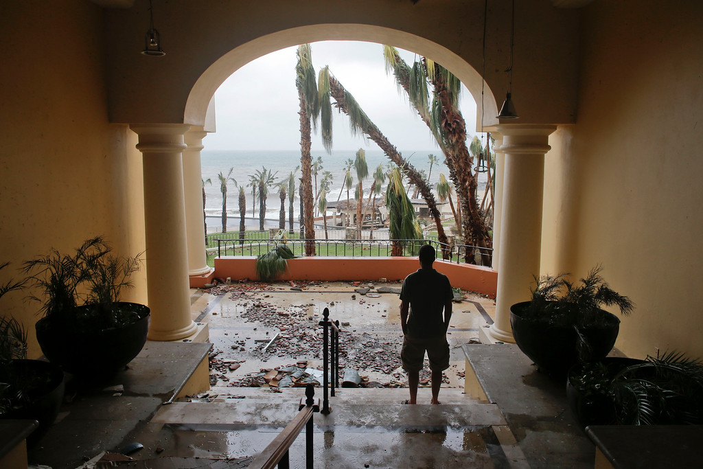 . A tourists looks to the ocean from inside a debris-filled area at the Hilton hotel after the resort sustained severe damage from Hurricane Odile in Los Cabos, Mexico,  Monday, Sept. 15, 2014.   (AP Photo/Victor R. Caivano)