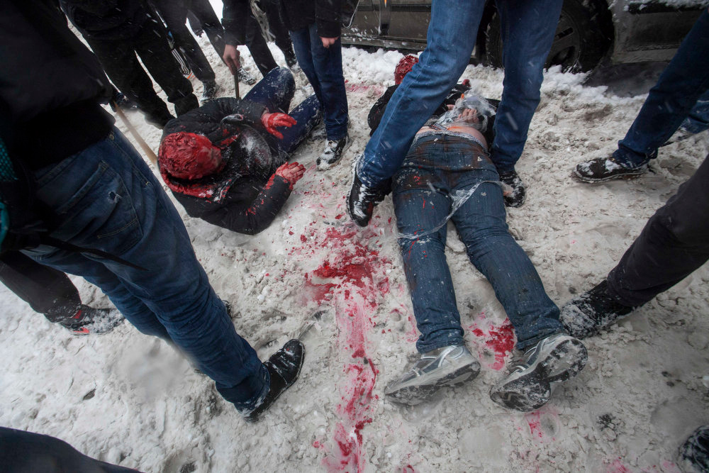 . In this photo taken on Friday, March 15, 2013, members of a pro-Kremlin youth group douse with red paint two tied-up pushers of spice, a synthetic drug, in Moscow, Russia. Russian officials and anti-drugs campaigners say that spice has become one of the most dangerous drugs widely available to youngsters and almost impossible to ban because of the constantly changing chemical ingredients. (AP Photo/Alexander Zemlianichenko Jr)