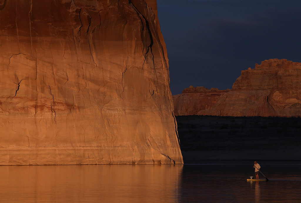 . A paddleboarder floats by Lone rock on Lake Powell on March 29, 2015 near Big Water, Utah. As severe drought grips parts of the Western United States, a below average flow of water is expected to flow through the Colorado River Basin into two of its biggest reservoirs, Lake Powell and Lake Mead. Lake Powell is currently at 45 percent of capacity, a recent study predicts water elevation there to be above 3,575 by September. The Colorado River Basin supplies water to 40 million people in seven western states.  (Photo by Justin Sullivan/Getty Images)