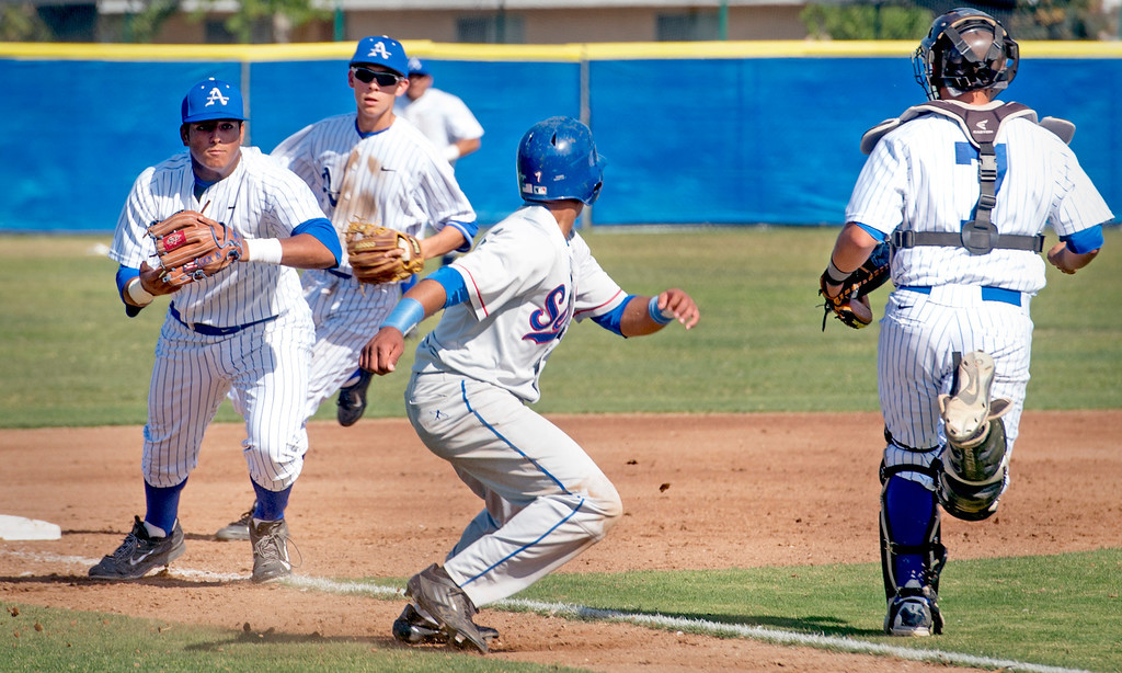. Serra High\'s Morgan Lomax, center, evades a Bishop Amat third inning rundown to score at Amat\'s La Puente, Calif. campus field April 16, 2014.  (Staff photo by Leo Jarzomb/San Gabriel Valley Tribune)
