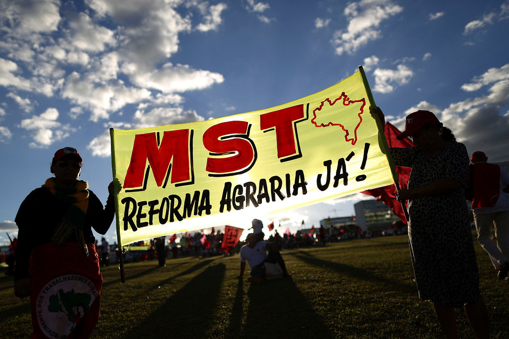 ". People hold a MST banner during the National Day of Struggle, a march by unionists, in Brasilia July 11, 2013. Union demonstrations snarled traffic in several Brazilian cities on Thursday morning as part of a one-day strike aimed at seizing the momentum of sweeping protests that shook Latin America\'s largest economy last month. The banner reads, ""MST - agrarian reform now!\"" REUTERS/Ueslei Marcelino"