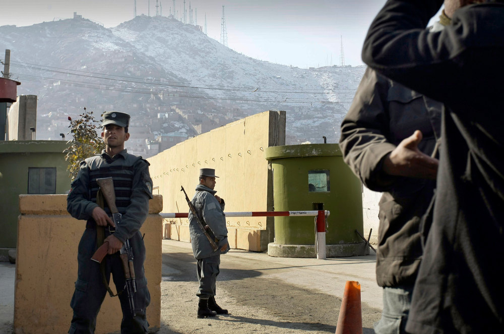 Description of . In this Monday, Dec. 24, 2012 file photo, Afghan police officers stand guard outside of Kabul police headquarters, where a an American contractor was killed, in Kabul, Afghanistan. On Tuesday, Dec. 25, 2012, the Interior Ministry said a policewoman, identified as Sgt. Nargas, who shot and killed 49-year-old Joseph Griffin in Kabul on Monday, was a native Iranian who came to Afghanistan and displayed