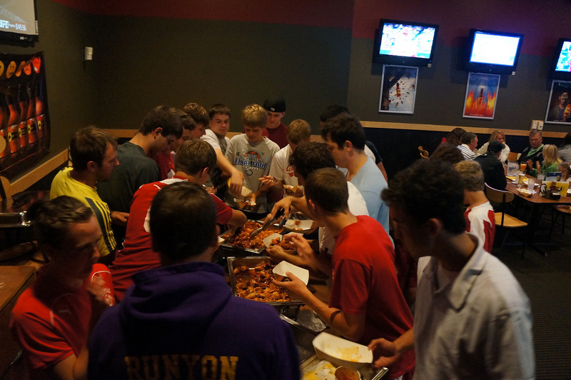 Players converge when more food arrives at Buffalo Wild Wings after the 10th Annual Alumni Soccer Game at Lutheran West.