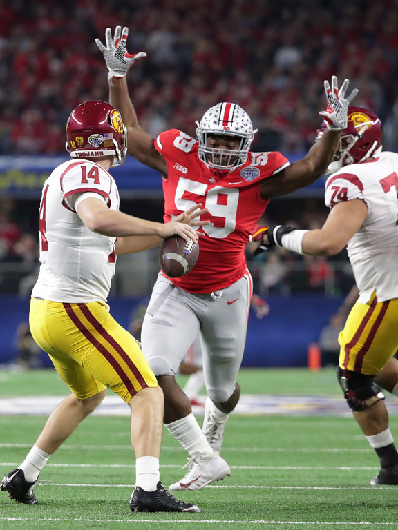 . Ohio State defensive lineman Tyquan Lewis (59) closes in on Southern California quarterback Sam Darnold (14) during the first half of the Cotton Bowl NCAA college football game in Arlington, Texas, Friday, Dec. 29, 2017. (AP Photo/LM Otero)