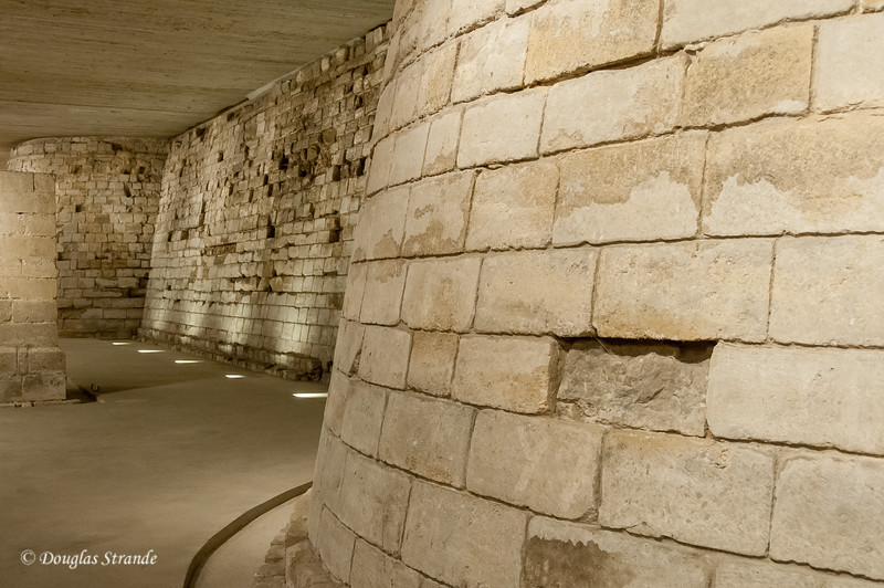 At the Louvre: Standing in the moat of the castle, looking at the base of the original walls.