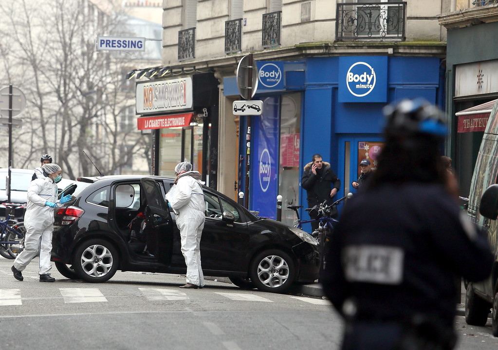 . Forensic experts examine the car believed to have been used as the escape vehicle by gunmen who attacked the French satirical newspaper Charlie Hebdo\'s office, in Paris, France, Wednesday, Jan. 7, 2015. Masked gunmen stormed the offices of a French satirical newspaper Wednesday, killing at least 11 people before escaping, police and a witness said. The weekly has previously drawn condemnation from Muslims. (AP Photo)