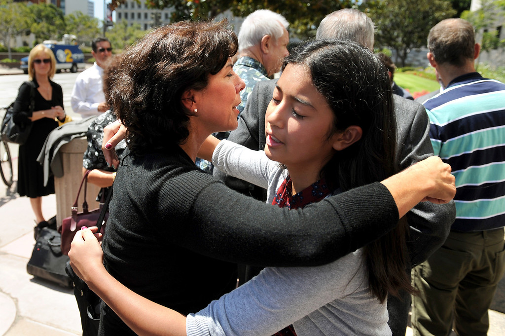 . Carol Champommier, center-left, hugs her niece Claire Champommier, 12, on the steps of the Federal Courthouse in downtown L.A., Wednesday, August 21, 2013, after being awarded $2 million of the $3 million judgement against the Federal government in the wrongful death lawsuit in the shooting death of her son Zachary Champommier. (Michael Owen Baker/L.A. Daily News)