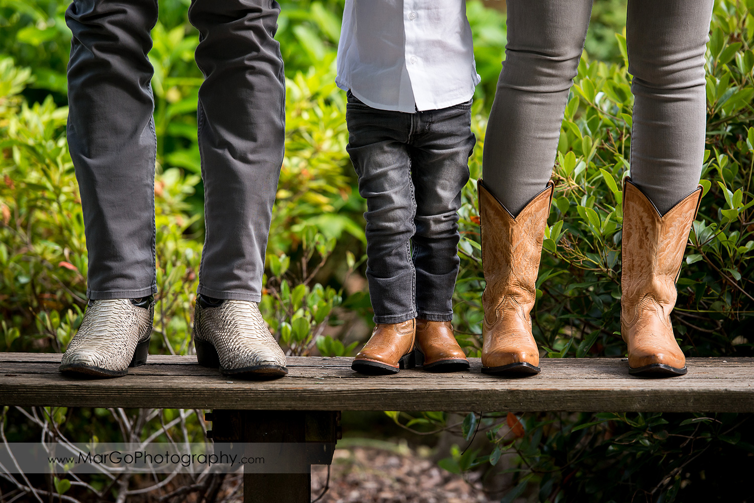 cowboy shoes of family of 3 wearing gray jeans in Shinn Historical Park and Arboretum in Fremont