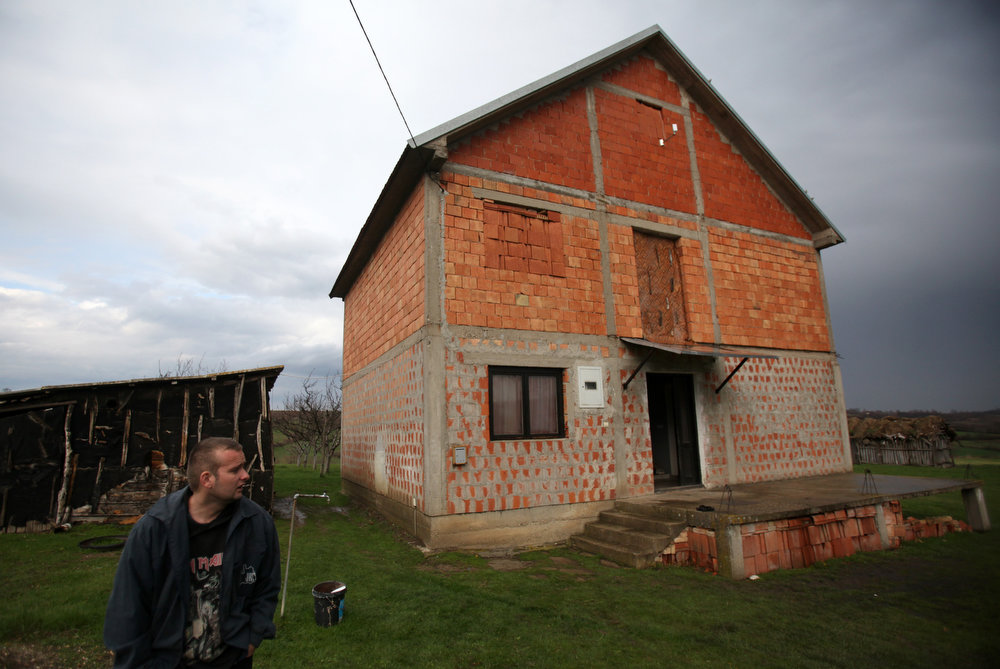 . Aleksandar Stekic stands in front house where his mother Dragana was shot to death while sleeping in the village of Velika Ivanca, Serbia, Tuesday, April 9, 2013. A 60-year-old man gunned down 13 people, including a baby, in a house-to-house rampage in a quiet village on Tuesday before trying to kill himself and his wife, police and hospital officials said. Belgrade emergency hospital spokeswoman Nada Macura said the man, identified as Ljubisa Bogdanovic, used a handgun in the shooting spree at five houses. The dead included six women. (AP Photo/Darko Vojinovic)