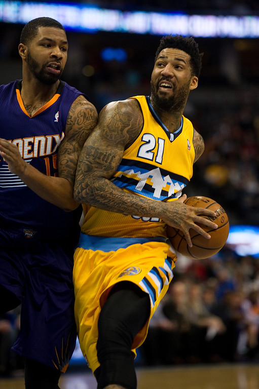 . DENVER, CO - DECEMBER 20: Wilson Chandler #21 of the Denver Nuggets drives against Marcus Morris of the Phoenix Suns during the first quarter of an NBA game at the Pepsi Center on December 20, 2013, in Denver, Colorado. (Photo by Daniel Petty/The Denver Post)