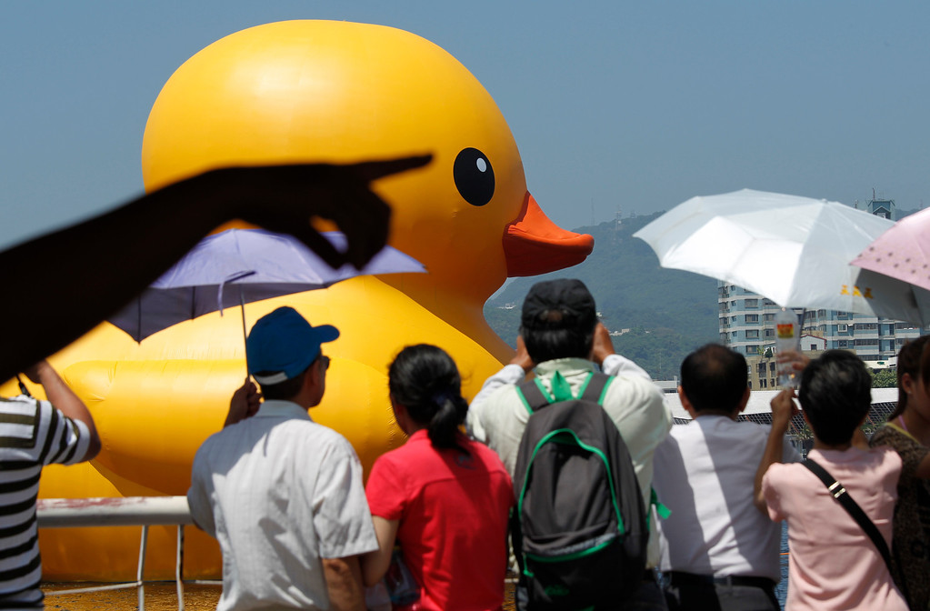 . Spectators watch a giant yellow duck arrive at the Glory Pier in the port of Kaohsiung, Taiwan, Thursday, Sept. 19, 2013.  (AP Photo/Wally Santana)