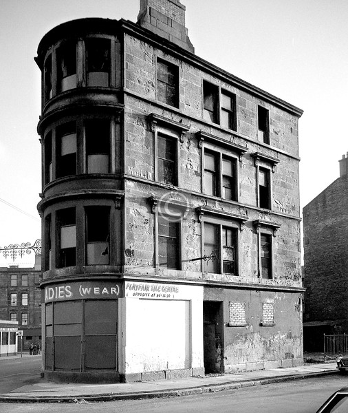 Floundering again. The flatiron shape of the tenement suggests the corner of Dalmarnock Rd and Old Dalmarnock Rd. The pub on the left, on the corner of, if I'm correct, Queen Mary St, is the Station Bar.  '1690' is daubed on the tenement wall across from it, which narrows it down to somewhere in west-central Scotland.   Update - I've just found this photo on a Youtube video, where it appears to have been lifted from a book which in turn must have lifted it from here. Anyway, the caption in the book identifies this, correctly I believe, as the corner of Dalmarnock Rd and Playfair St. The tenement in the distance is in Mordaunt St.    January 1976