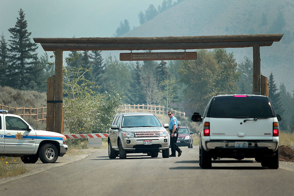 . A member of the Blaine County Sheriff Department directs traffic along Green Horn Gulch Road, that has been closed west of Idaho Highway 75 from the 44,000 acre Beaver Creek Fire on Thursday, Aug. 15, 2013 south of Ketchum, Idaho. (AP Photo/Times-News, Ashley Smith)