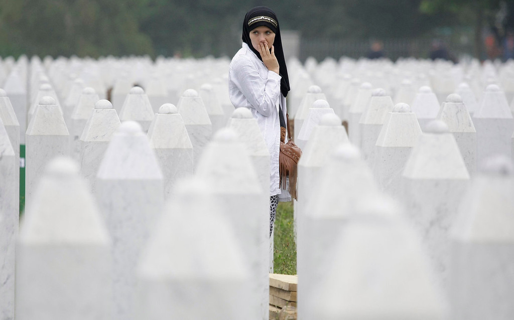 . Bosnian woman Merima Nukic searches for her father\'s grave among gravestones during a funeral ceremony at the memorial center in Potocari, near Srebrenica, 160 kms east of Sarajevo, Bosnia, Thursday, July 11, 2013. People from around Bosnia and abroad have begun arriving in Srebrenica Thursday to commemorate 18th anniversary of the 1995 massacre and rebury recently identified victims exhumed from mass graves. The victims\' bodies are still being exhumed from mass graves in the area, where Serbs had dumped them in an attempt to cover up the crime. Identified victims are buried each year on the massacre\'s anniversary at a memorial cemetery near Srebrenica. (AP Photo/Amel Emric)
