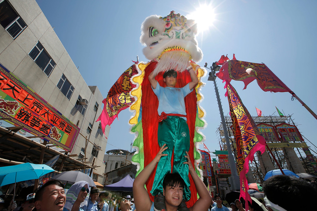 . Villagers perform lion dance during a parade on the outlying Cheung Chau island in Hong Kong to celebrate the Bun Festival Tuesday, May 22, 2018. Bun Festival, the Taoist God of the Sea, is worshipped and evil spirits are scared away by loud gongs and drums during the procession. The celebration includes bun scrambling, parades, opera performances, and children dressed in colorful costumes. (AP Photo/Kin Cheung)