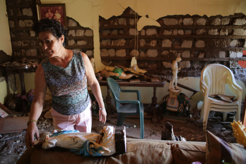 . A woman picks up a religious image inside her home, damaged by an earthquake on the eve, in Nagarote, some 40 Km from Managua, on April 11, 2014. A 6.2-magnitude earthquake that struck Nicaragua killed one person, left 33 injured and damaged more than 800 homes, the government said Friday.  (Inti Ocon/AFP/Getty Images)
