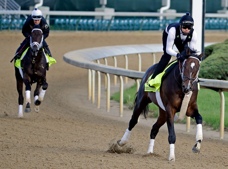 . Exercise rider Emerson Chavez takes Kentucky Derby entrant Commanding Curve for a morning workout with exercise rider Isabelle Bourez riding  Intense Holiday, behind, at Churchill Downs Thursday, May 1, 2014, in Louisville, Ky. (AP Photo/Morry Gash)