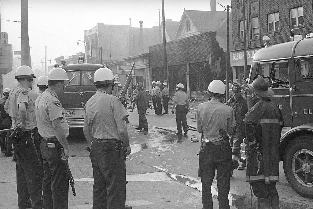 . Cleveland police, wearing riot helmets and some armed with shotguns, protect firemen working on Hough Avenue in Cleveland, July 23, 1966. Police protection was ordered after three persons were arrested for heckling and abusing firemen. Several buildings were burned last night when rioting swept the predominantly black east side area. (AP Photo/Julian C. Wilson)