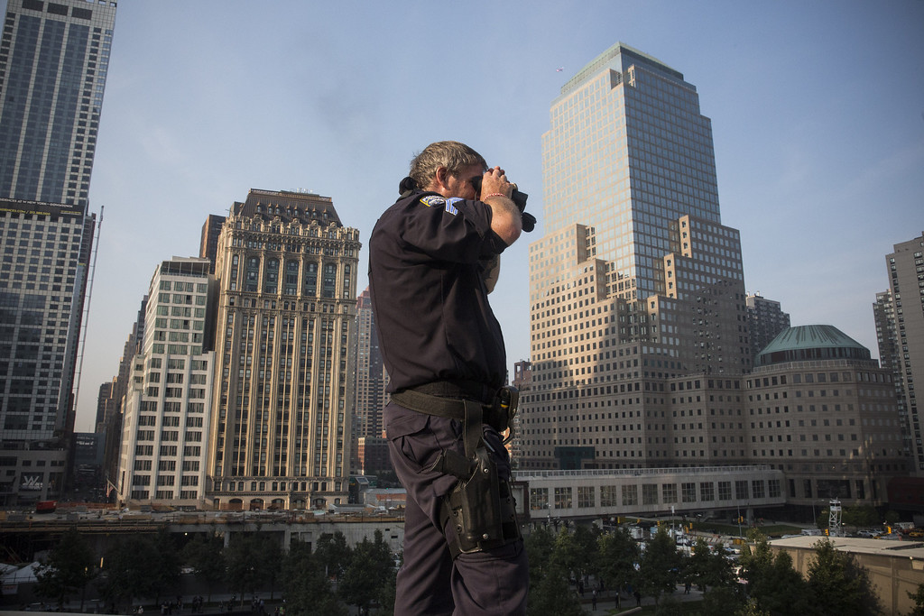 . Sgt. Keven Cottrell, of the Port Authority Emergency Services Unit, monitors Ground Zero during memorial ceremonies for the twelfth anniversary of the terrorist attacks on lower Manhattan at the World Trade Center site on September 11, 2013 in New York City. T (Photo by Andrew Burton/Getty Images)