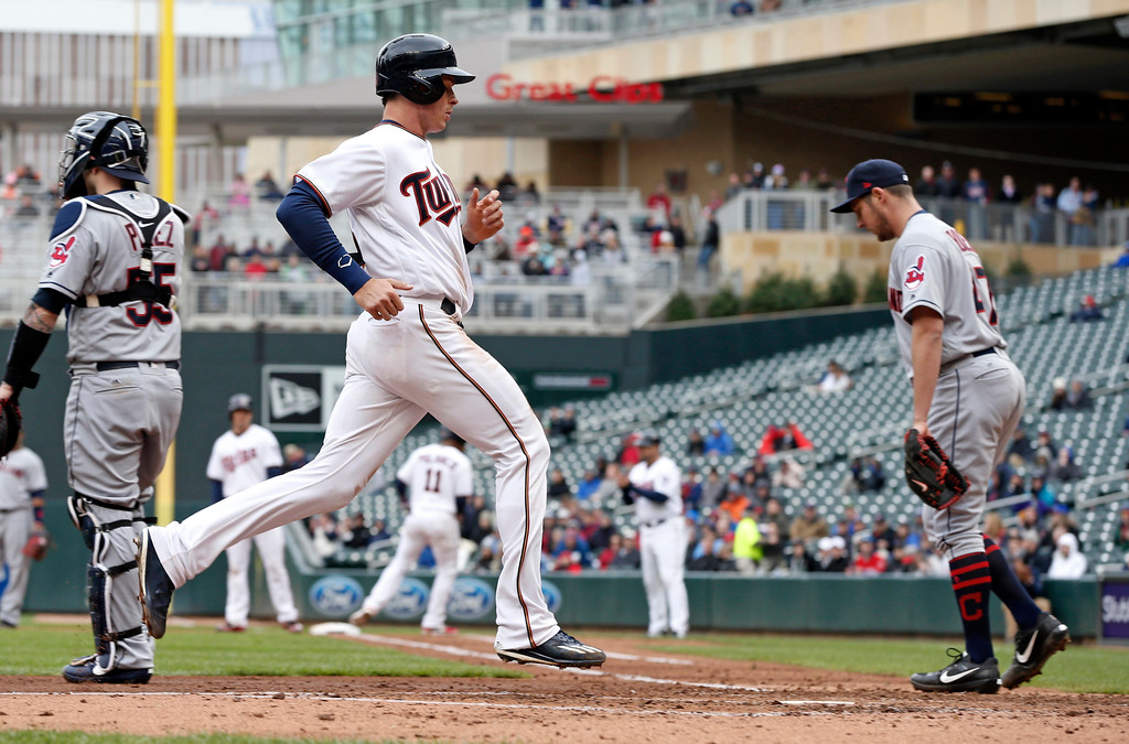 . Cleveland Indians pitcher Trevor Bauer, right, returns to the mound after backing up the plate as Minnesota Twins\' Max Kepler scores on a sacrifice fly by Jorge Polanco in the fourth inning of a baseball game Thursday, April 20, 2017, in Minneapolis. (AP Photo/Jim Mone)