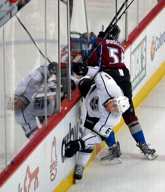 . Colorado Avalanche left wing Patrick Bordeleau (58) avoids a hit by Los Angeles Kings defenseman Jake Muzzin (6) as he slams n to the dasher boards during the second period February 27, 2014 at Pepsi Center. (Photo by John Leyba/The Denver Post)