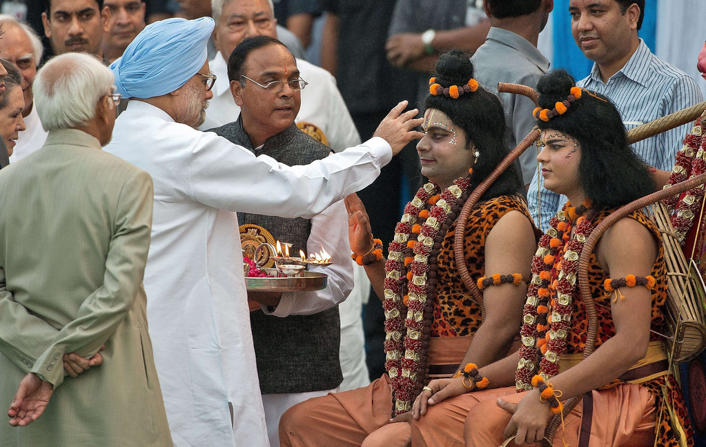 . Indian Prime Minister Manmohan Singh (2R) performs a religious ritual over performers dressed as Hindu God Rama (C) ahead of the burning of the effigy of the Ravana, during the Hindu festival of Dussehra in New Delhi on October 13, 2013. Dussehra, which is celebrated at the end of the Navratri (nine nights) festival, symbolises the victory of good over evil in Hindu mythology. On the night of Dussehra fire-cracker stuffed effigies of demon king Ravana are set ablaze across the country.   PRAKASH SINGH/AFP/Getty Images